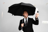 jóképű és mosolygós üzletember öltönyben, kezében esernyővel és szürke alapon elszigetelt dollárbankjeggyel.