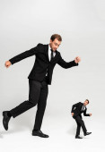 rozzlobený podnikatel v obleku bít vystrašený loutka na šedém pozadí