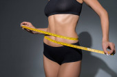 cropped view of slim woman in underwear holding measuring tape on waist on dark background