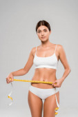 beautiful slim woman in underwear holding measuring tape on waist isolated on grey