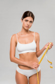 sad beautiful slim woman in underwear holding measuring tape isolated on grey