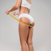 Ausgeschnittene Ansicht einer schlanken Frau in Unterwäsche, die Maßband unter dem Gesäß hält, isoliert auf grau