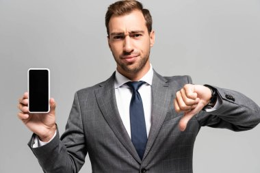 sad businessman in suit holding smartphone and showing dislike isolated on grey