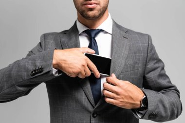cropped view of businessman in suit hiding smartphone isolated on grey