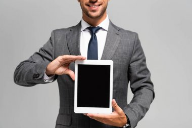 Cropped view of smiling businessman in suit holding digital tablet isolated on grey stock vector