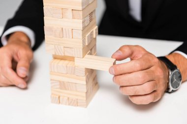 cropped view of businessman in suit playing blocks wood game