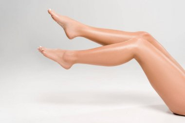 cropped view of beautiful female legs on grey background