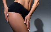 oříznutý pohled na krásnou štíhlou ženu ve spodním prádle dotýkající se nohy na černém pozadí