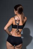Fotografie Rückseite der schönen Frau in Unterwäsche mit Handschellen auf schwarzem Hintergrund