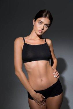 beautiful slim woman in underwear posing on black background