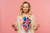 Mosolygó szőke nő gazdaság amerikai és brit zászlók elszigetelt rózsaszín