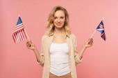 Vonzó szőke nő gazdaság amerikai és brit zászlók elszigetelt rózsaszín