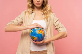 Fotografie Cropped view of blonde woman holding globe isolated on pink