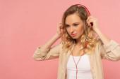 Atraktivní blondýny ve sluchátkách izolované na růžové