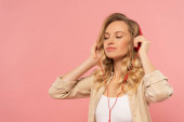 Blonde woman with closed eyes in headphone isolated on pink
