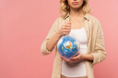 Fotografie Cropped view of woman holding globe in polyethylene pack isolated on pink, global warming concept