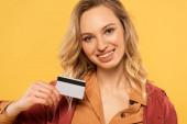 Usmívající se žena držící kreditní kartu izolované na žluté