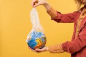 Vágott kilátás a női gazdaság földgömb és műanyag csomag elszigetelt sárga, globális felmelegedés koncepció