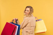 Smiling blonde woman holding shopping bags in hands isolated on yellow