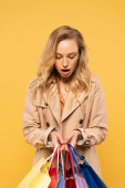 Surprised woman holding shopping bags isolated on yellow