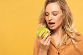 Fiatal nő fogszabályzó harapás zöld alma izolált sárga