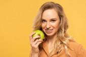 Lächelnde blonde Frau mit Zahnspange, die grünen Apfel isoliert auf gelb hält