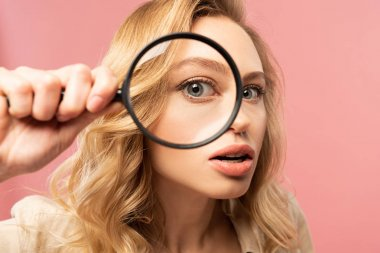 Blonde woman looking throughout magnifying glass isolated on pink