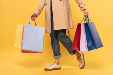 Cropped view of woman holding shopping bags in hands on yellow background