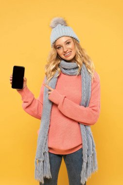 Smiling woman in hat and scarf pointing on smartphone with blank screen isolated on yellow stock vector