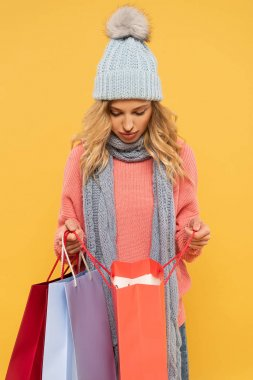 Woman in hat and scarf looking in shopping bags isolated on yellow