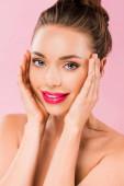 mosolygós meztelen gyönyörű nő rózsaszín ajkak pózol a kezét az arcon elszigetelt rózsaszín