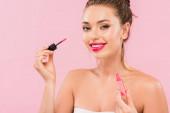 sorridente nuda bella donna con labbra rosa tenendo il labbro lucido isolato su rosa