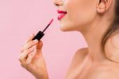 oříznutý pohled na usmívající se nahá krásná žena s růžovými rty nanášení lesk na rty izolované na růžové