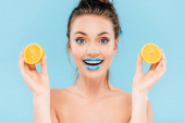 excited naked beautiful woman with blue lips holding orange halves isolated on blue