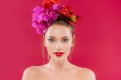 nahá krásná žena s červenými rty a květinovým věncem na hlavě izolované na karmínu