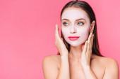 Fotografie nackte schöne Frau in Gesichtsmaske mit Händen in Gesichtsnähe isoliert auf rosa