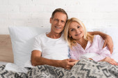 Smiling mature couple holding hands and looking at camera in bed