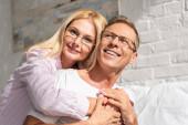 Usmívající se pár v pyžamu a brýle objímání v ložnici v dopoledních hodinách