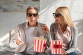 reifes Paar in 3D-Gläsern mit Eimern mit Popcorn auf dem Bett