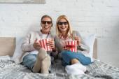 Lächelndes Paar in 3D-Gläsern mit Popcorn-Eimern auf dem Bett