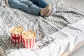 Cropped vista della coppia sdraiato sul letto accanto secchi popcorn e bicchieri 3d