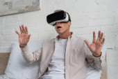 Aufgebrachter Mann in Virtual-Reality-Headset auf Bett