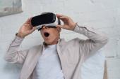 Šokovaný muž ve virtuální realitě sluchátka hrát videohry na posteli