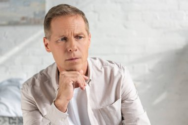 Worried man with hand on chin looking away at home