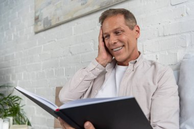 Exited man looking in notebook while sitting on bed