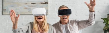 Panoramic shot of exited couple in virtual reality headsets