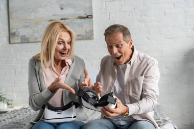 Exited couple looking at virtual reality headset on bed