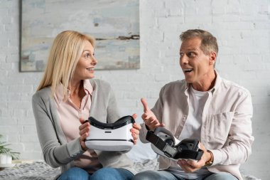 Exited couple holding virtual reality headsets on bed