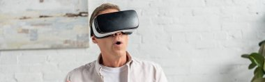 Exited man in virtual reality headset at home, panoramic shot
