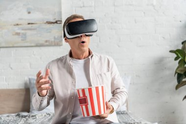 Exited man in virtual reality headset with popcorn on bed